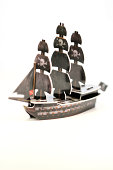 """Vancouver,Canada - February 26, 2013: A paper pirate ship from the constructible strategy game Pirates of the Spanish Main produced by WizKids, posed against a black background."""