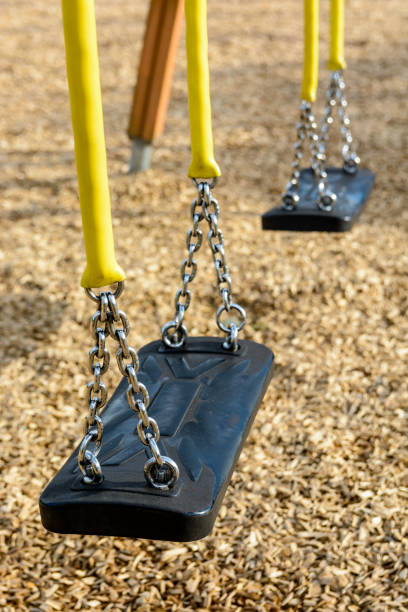 A still child's swing in black plastic in a wood chips covered playground with chrome chains in a yellow plastic sleeve A still child's swing in black plastic in a wood chips covered playground with chrome chains in a yellow plastic sleeve. amortize stock pictures, royalty-free photos & images