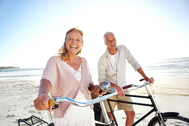 Still in great shape despite their age Happy senior couple standing on the beach with their bicycles despite stock pictures, royalty-free photos & images