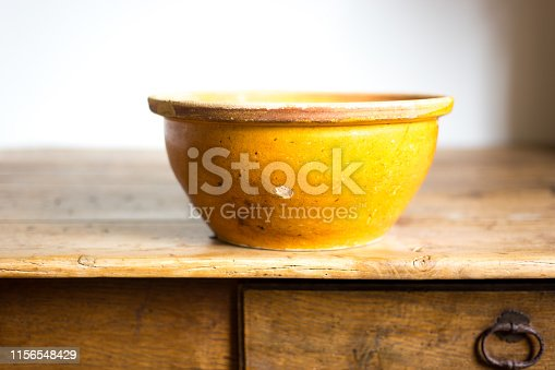 Still life: Antique Yellow Bowl on old wood table. White background with lots of copy space.