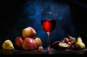 istock Still life, apples, grapes, fruit and red juice on a dark blue background. 1078540524
