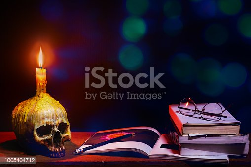 istock Still life art of wizard wooden desk with skull of lighting candle and books with glasses on with a pencil in in dark blue tone background, concept of wisdom in the dark 1005404712