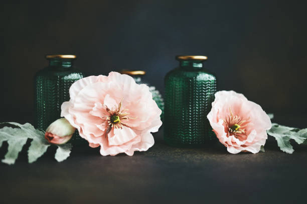 Still life background with small glass jars and pink poppies stock photo