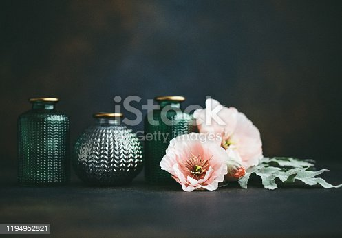 Still life background with small glass jars and pink poppies