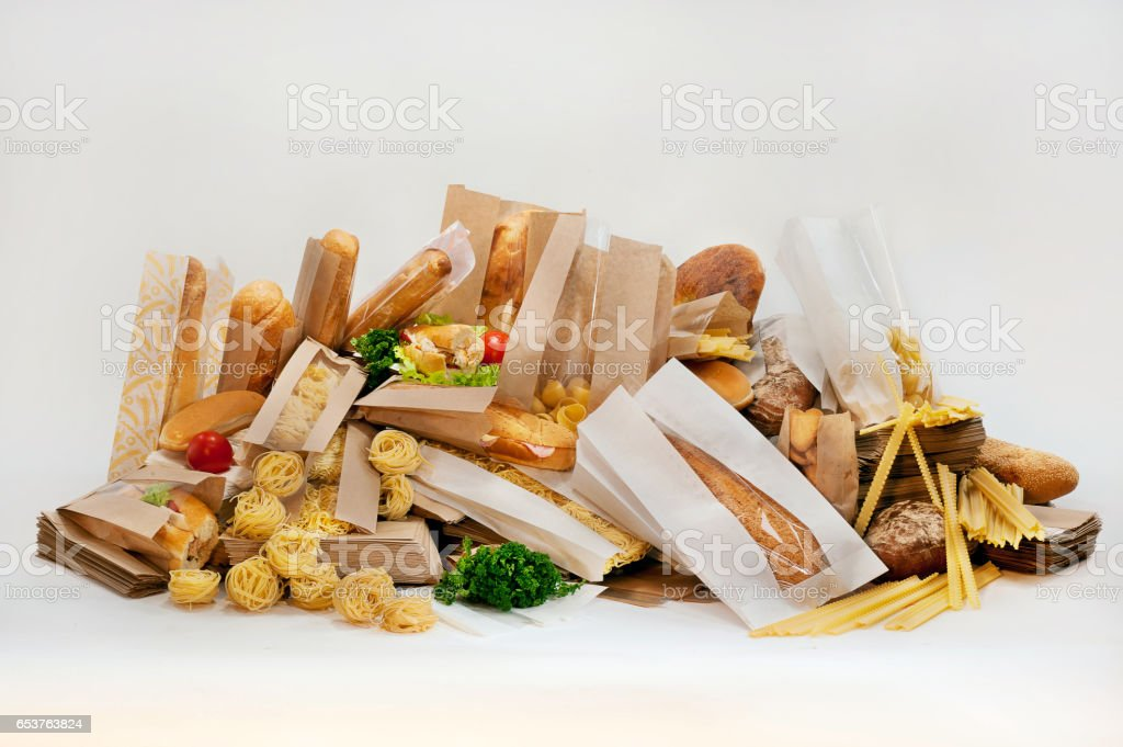 Still Life baguette loaf of bread and other various in paper packaging. Pasta and cookies in paper bags. Salad and vegetables. – Foto
