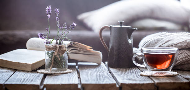 still life book and a cup of tea in the living room - top view, wood table, empty imagens e fotografias de stock