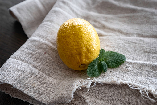 Still life consisting of lemon ,mint leaves and vintage towel. Healthy and natural tea ingredients.