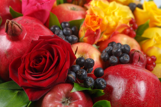 Still life consisting of pomegranates, apples, black rowan, red viburnum, pears, lemons and flowers of red and yellow roses close-up stock photo