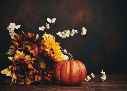 Still life fall Thanksgiving arrangement with sunflowers and pumpkin