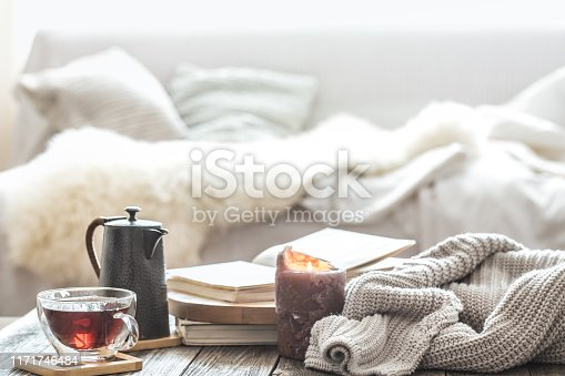 Still life home comfort in the living room with a Cup of tea and a kettle , near a burning candle and a knitted sweater.The concept of home atmosphere and comfort