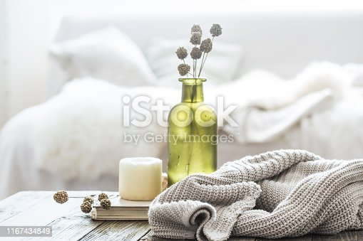 Still life home decor on a wooden table in the living room. decorative bottle with flowers and a candle near a knitted sweater.