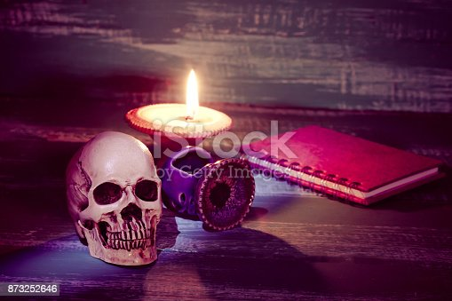 istock still life human skull and old book with candlestick 873252646
