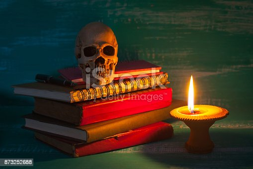istock still life human skull and old book with candlestick 873252688