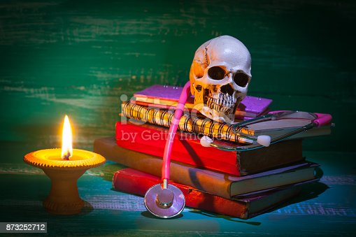istock still life human skull and old book with candlestick 873252712