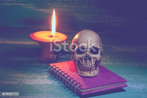 istock still life human skull and old book with candlestick 873252722