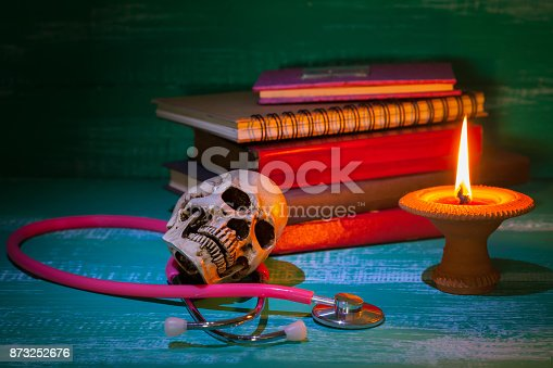 istock still life human skull on stethoscope and old book with 873252676
