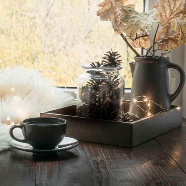 stillleben in wohngebäude. tasse kaffee zu hause, girlande, schwedische hygge konzept. - fensterdeko herbst stock-fotos und bilder