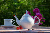 still life in the morning garden with white teapot, cup, strawberries and purple roses.