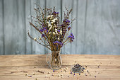 Still life of a bouquet of dried flowers in a glass jug on a wooden table.