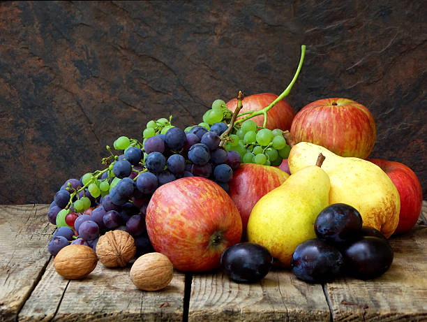 still life of autumn fruits: grapes, apples, pears, plums, nuts stock photo