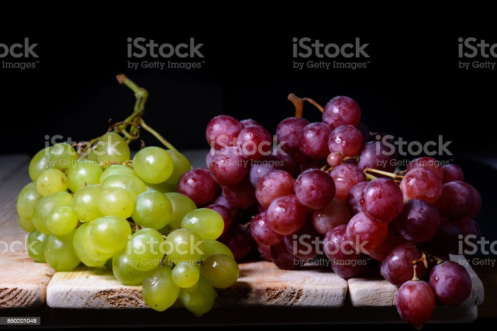 still life of bunches of red grapes and green, on wooden table. stock photo