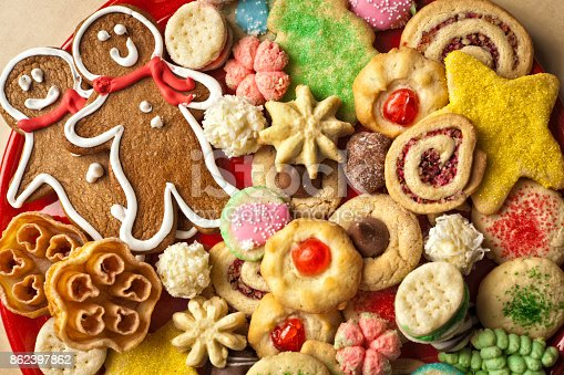 A colorful and festive plate of Christmas Cookies. Still life photographed on wooden table with copy space.