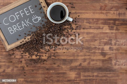 This is a bird's eye view of a full coffee cup with saucer and coffee grounds and beans scattered on a rustic wooden surface.  They lay in the corner with a wooden