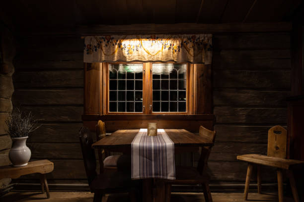 Still life of dark and rustic old fashioned interior decor in nineteenth century style. Timber and wooden oak furniture in front of a window. stock photo