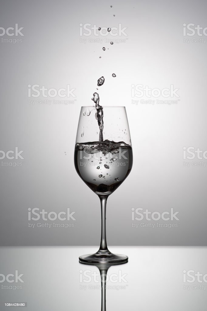 Still life of drinking glasses on gray gradient background: one glass...