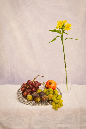still life of flowers and fruits on an earth colored background, with grapes, figs, a pomegranate on a silver plate and a yellow lily a glass jar, vertical