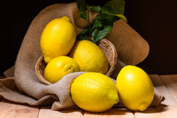 still life of lemons with green leaves on wood, burlap and wicker basket stock photo