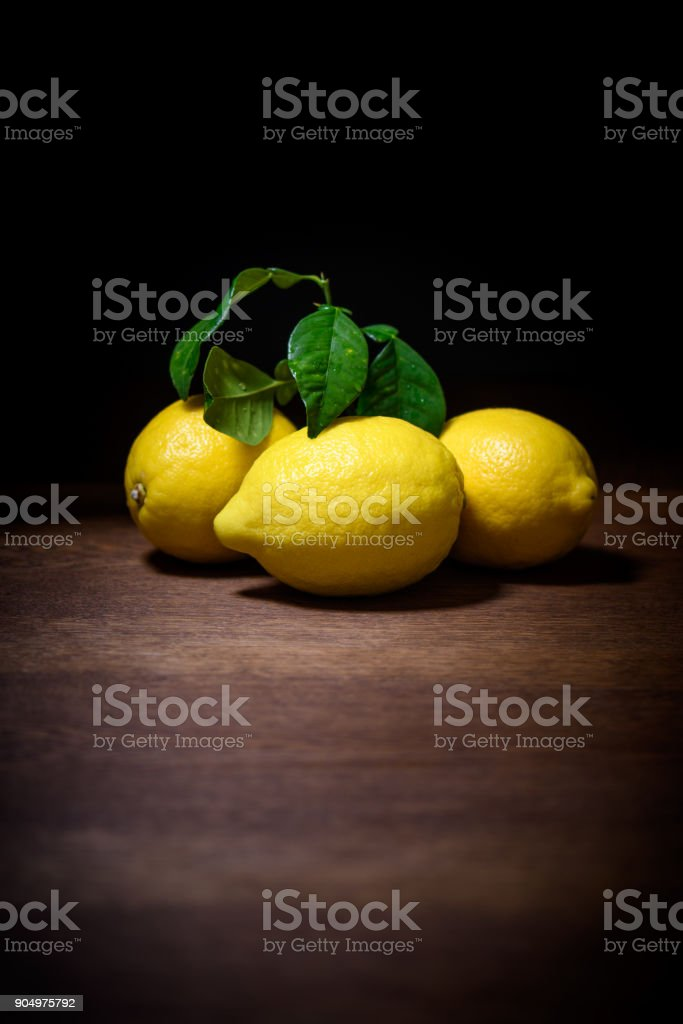 still life of lemons with green leaves on wood stock photo