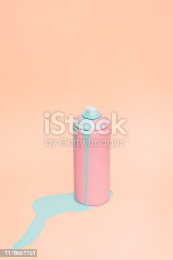 Clean still life picture of pink spray can. There blue paint flowing out of it. Taken on pink background.