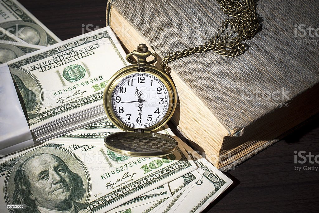 Still life of pocket watch on bills and old book stock photo
