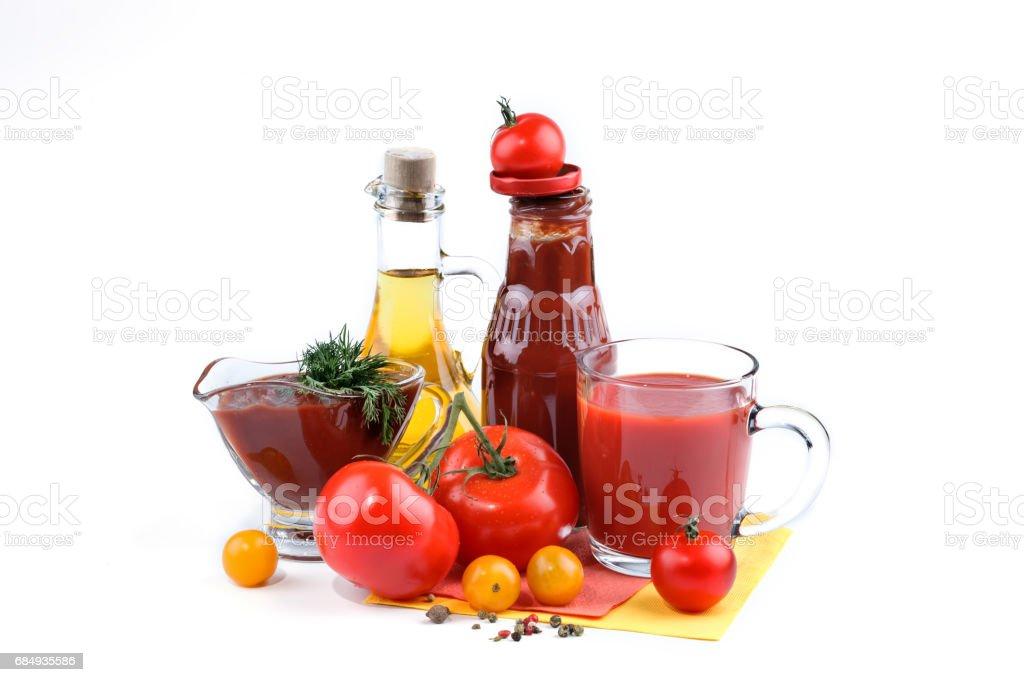 Stillleben mit roten und gelben Tomaten, Flasche Tomatensauce und Olivenöl auf weißem Hintergrund Lizenzfreies stock-foto