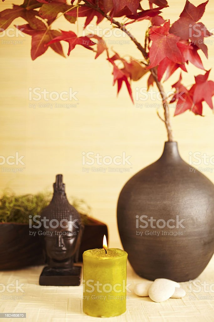 Still life of red maple leaves in vase with buddha royalty-free stock photo