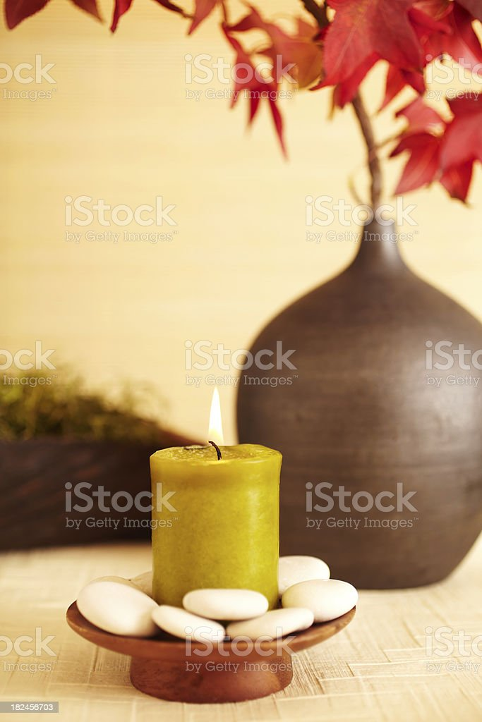 Still life of red maple leaves in vase with candle royalty-free stock photo
