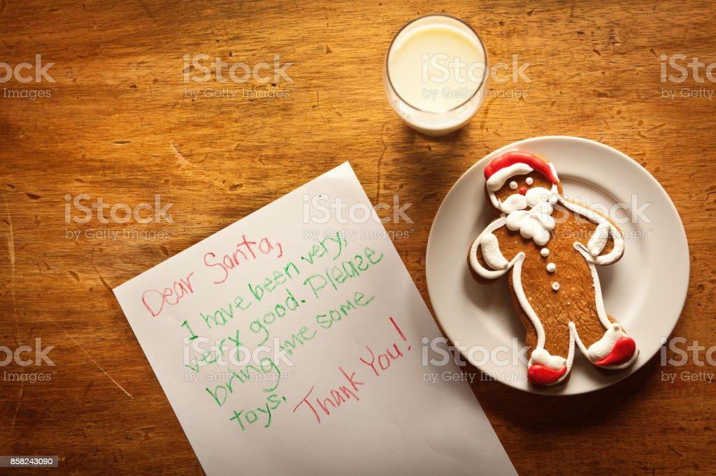 Still life of Santa Christmas Cookie, Milk and Children Letter to Santa stock photo