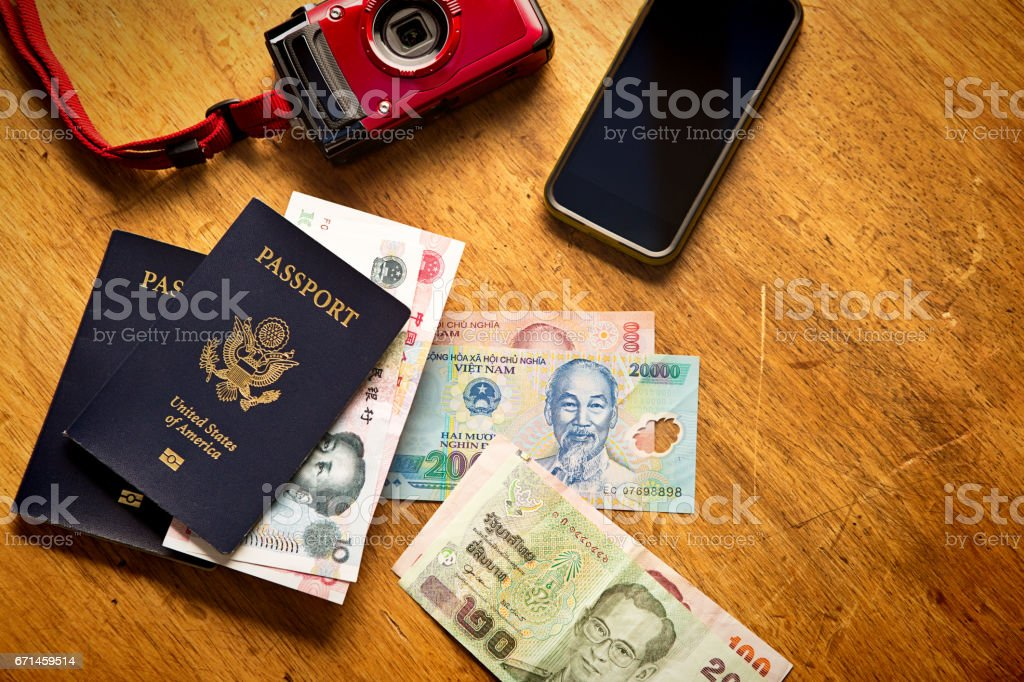 Still Life of Travel Essentials Passport, Asian Currency, Camera and Phone stock photo