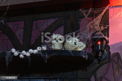 1176385551istockphoto Still life of two skulls on a shelf with a bundle of garlic 1176385551