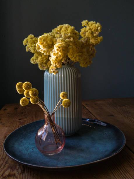 fortfarande liv av vas med gula blommor på en blå platta bildbanksfoto