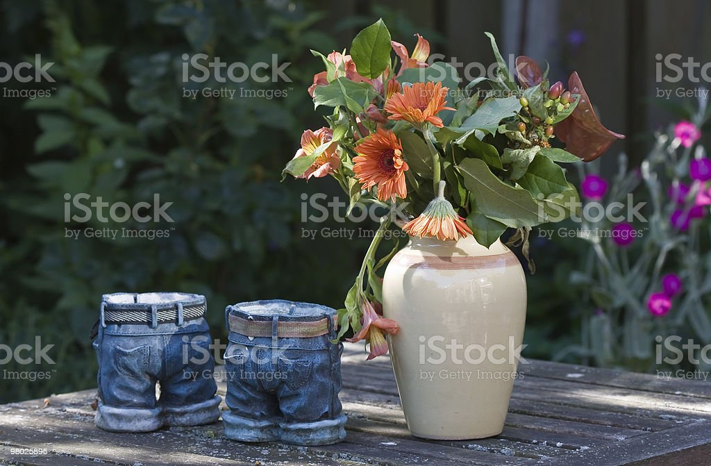 Still life of vases and flowers at a garden table royalty-free stock photo