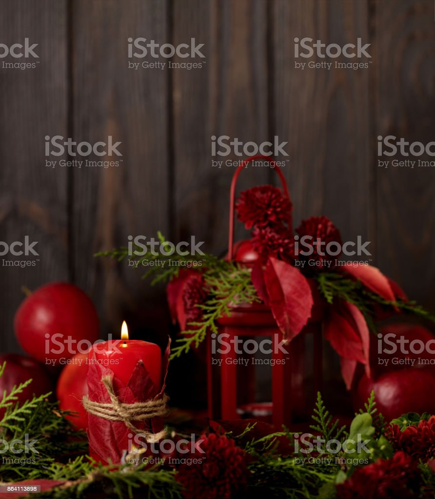 Still life on a dark background. Decor of candles and candlesticks with juniper, daisies and red leaves. royalty-free stock photo