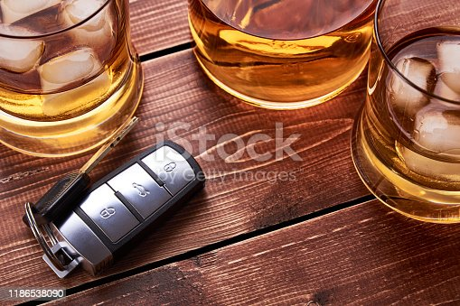 Still life on old wooden table top. Car keys, several glasses and a bottle of whiskey or alcohol. Suitable for drunk driving.