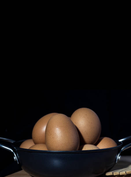 Still Life Organic Eggs in Metal Pan on the Dark Background stock photo