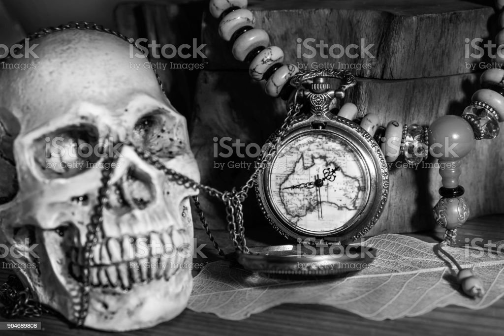 Still life photography pocket watch , bead necklace and blured human skulls in black adn white stock photo