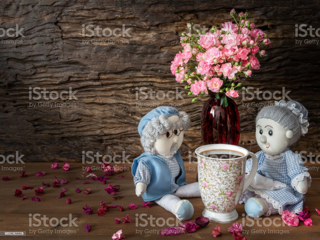 Still life visual art of grandparent dools sitting with a cup of coffee and pink rose in red vase with dried flowers falled around on wooden floor with wooden slab background royalty-free stock photo