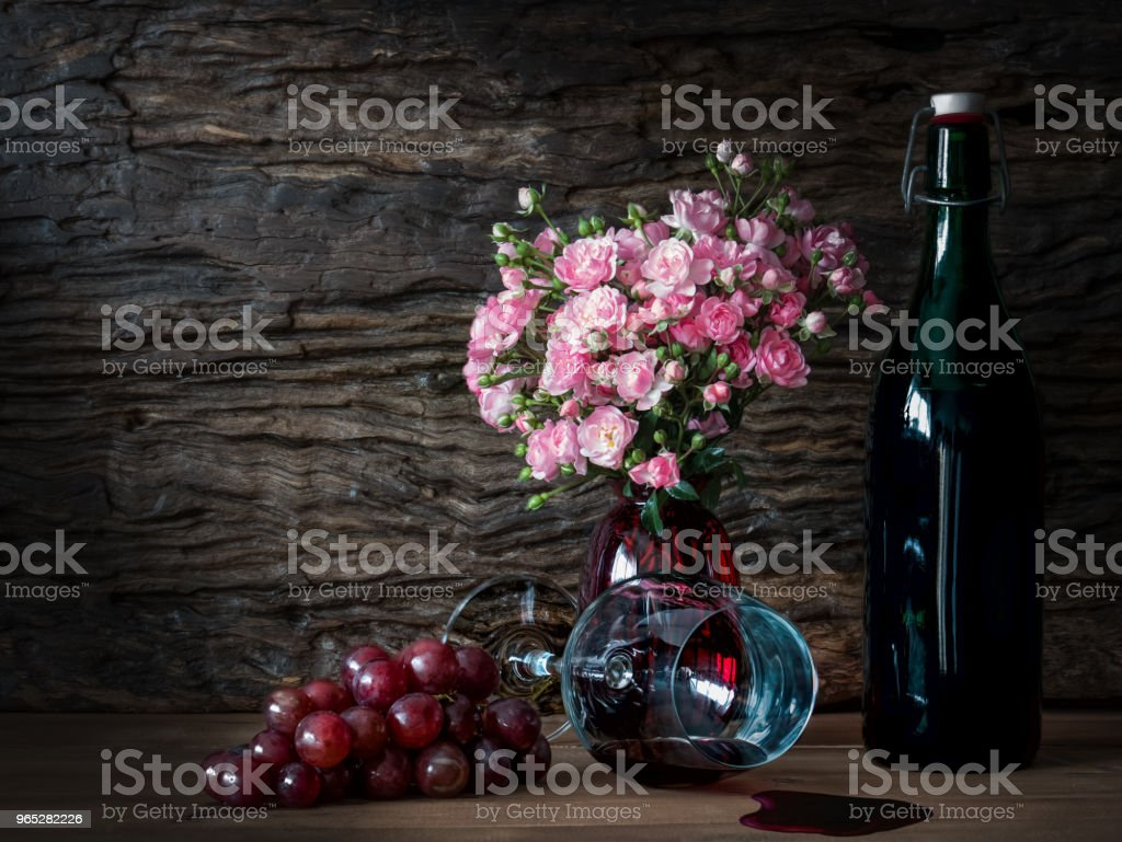 Still life visual art of grapes, a falled glass of wine, a bottle of wine and pink roses in a red vase on wooden slab with wooden back drop royalty-free stock photo
