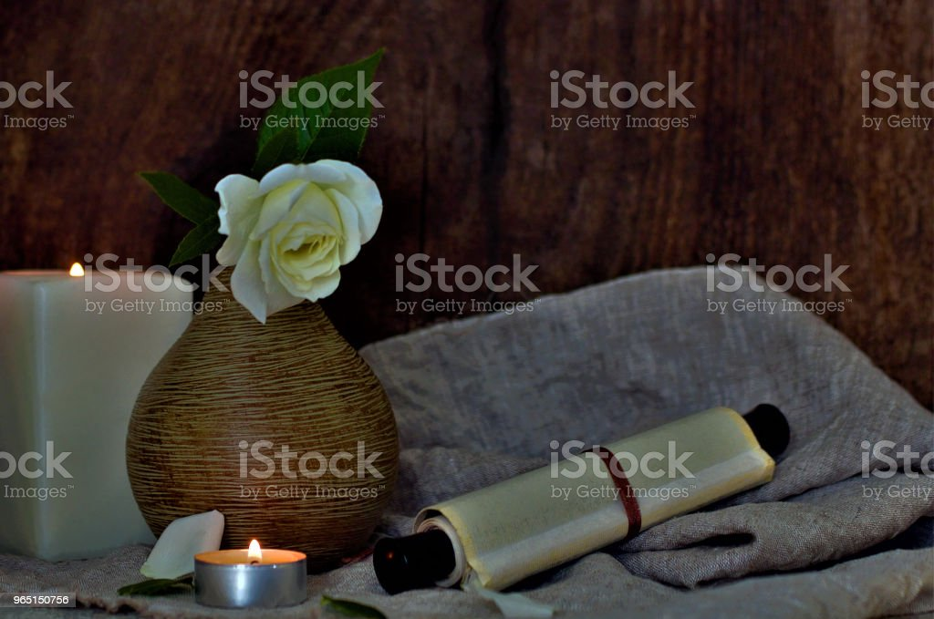 Still life with a beautiful flower. A white rose in a vase. On the table is a coarse cloth and a scroll. Lifestyle wabi sabi. royalty-free stock photo