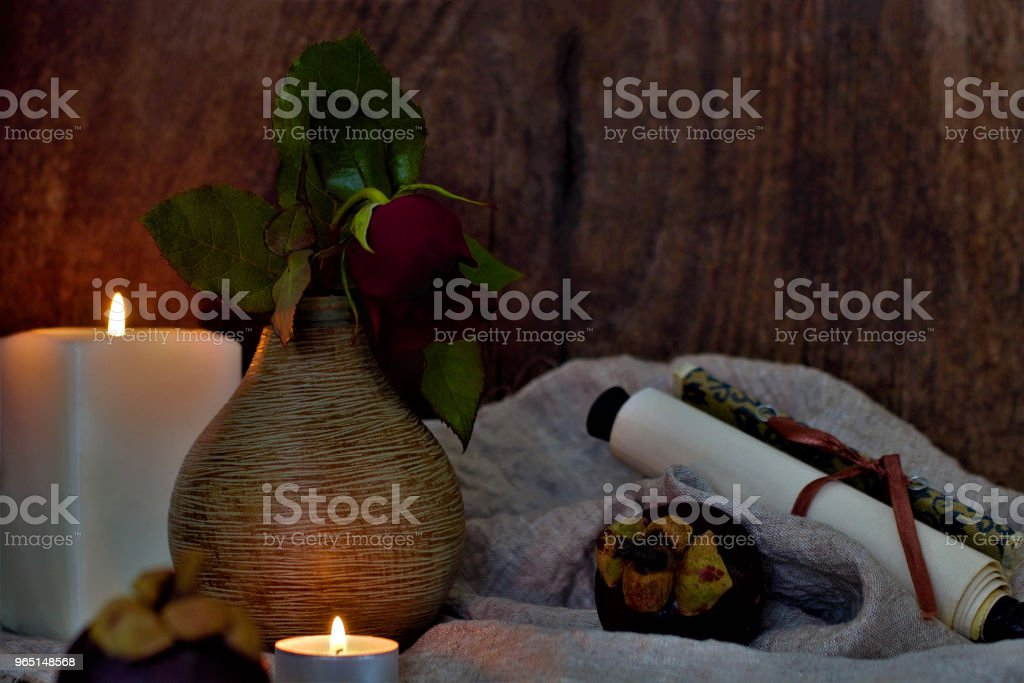 Still life with a beautiful flower. Red rose in a vase. On the table is a rough fabric, an exotic fruit and a scroll. Lifestyle wabi sabi. royalty-free stock photo